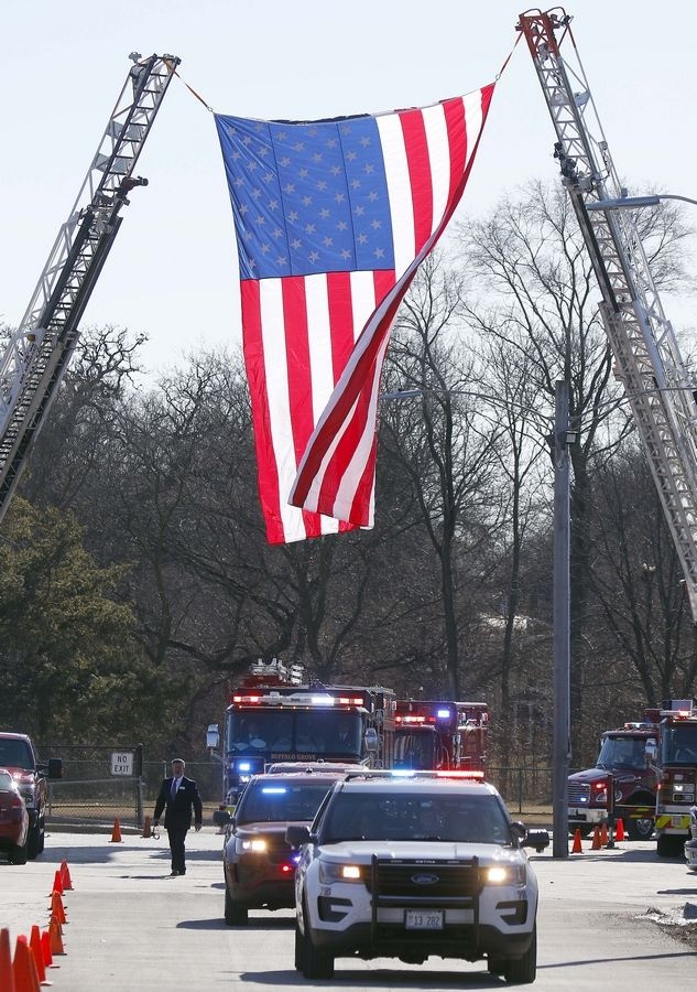 A giant flag hung between two ladder trucks greets Buffalo Grove firefighter/paramedic Kevin Hauber, 51, Friday at St. Mary's Church in Buffalo Grove. Hauber died last weekend after a four-year battle with colon cancer.