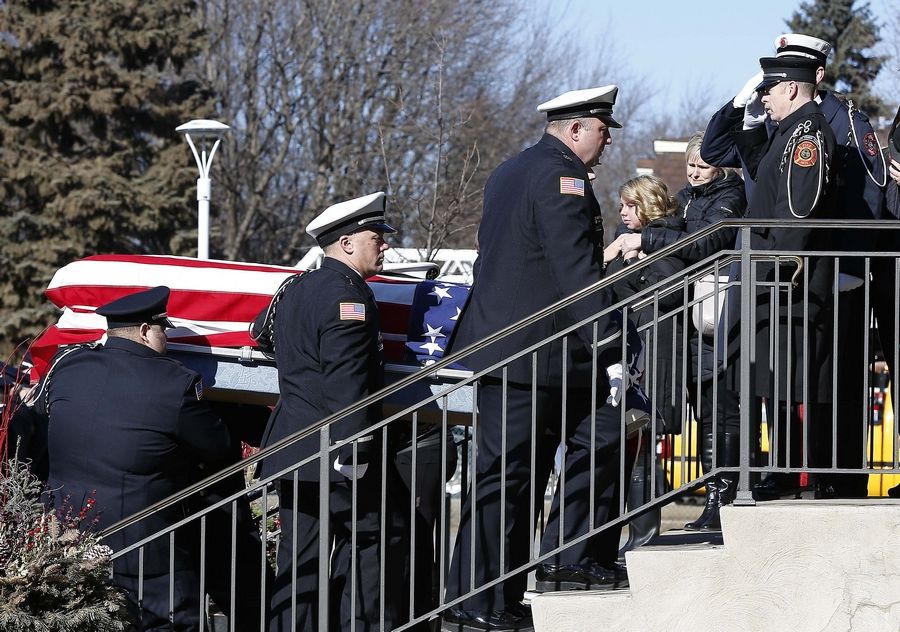 Buffalo Grove firefighter/paramedic Kevin Hauber, 51, died last weekend after a four-year battle with colon cancer. Firefighters, friends and family line up at Hauber's funeral Mass Friday at St. Mary's Church in Buffalo Grove.