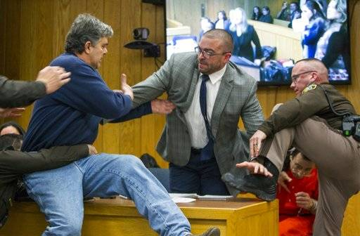 Randall Margraves, father of three victims of Larry Nassar , left, lunges at Nassar, bottom right, Friday, Feb. 2, 2018, in Eaton County Circuit Court in Charlotte, Mich.  The incident came during the third and final sentencing hearing for Nassar on sexual abuse charges. The charges in this case focus on his work with Twistars, an elite Michigan gymnastics club.   (Cory Morse/The Grand Rapids Press via AP)