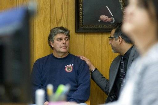 Randall Margraves, left, talks to attorney Mick Grewal, as he prepares to stand in front of Judge Janice Cunningham for a contempt of court hearing after he lunged at Larry Nassar during Nassar's sentencing at Eaton County Circuit Court in Charlotte, Mich., on Friday, Feb. 2, 2018.   Cunningham accepted an apology from Margraves, the father of three victims of Nassar.  A lawyer and sheriff's deputies stopped Margraves before he could reach Nassar, who is being sentenced for sexually assaulting gymnasts.    (Cory Morse/The Grand Rapids Press via AP)
