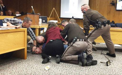 Eaton County Sheriff's deputies restrain Randall Margraves, father of three victims of Larry Nassar, Friday, Feb. 2, 2018, in Eaton County Circuit Court in Charlotte, Mich.  The incident came during the third and final sentencing hearing for Nassar on sexual abuse charges. The charges in this case focus on his work with Twistars, an elite Michigan gymnastics club.  (Kim Kozlowski/Detroit News via AP)
