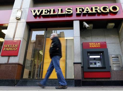 FILE - In this Wednesday, Dec. 19, 2012, file photo, a man walks past a Wells Fargo location in Philadelphia. The Federal Reserve is imposing more penalties on Wells Fargo, freezing the bank's growth until it can prove it has improved its internal controls. The new penalties were announced late Friday, Feb. 2, 2018, on Fed Chair Janet Yellen's last day at the central bank.