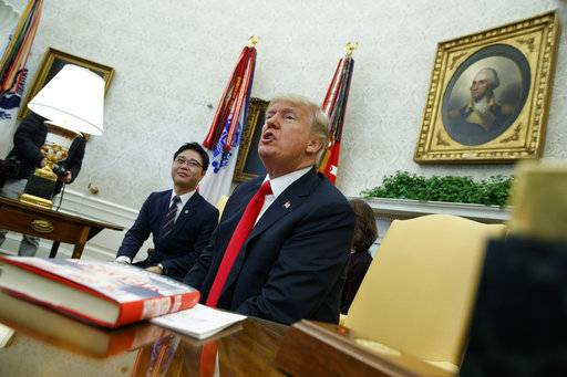 President Donald Trump speaks with reporters about allowing the release of a secret memo on the FBI's role in the Russia inquiry, during a meeting with North Korean defectors in the Oval Office of the White House, Friday, Feb. 2, 2018, in Washington.