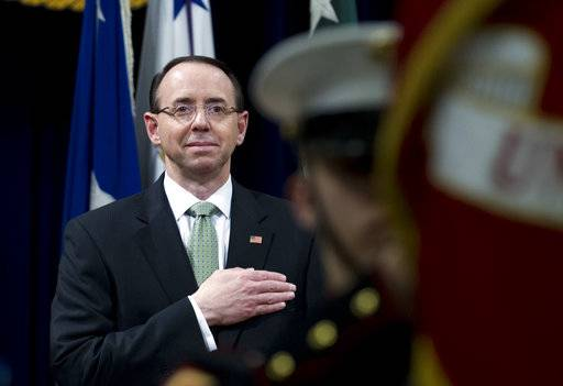 Deputy Attorney General Rod Rosenstein listen the national anthem during the opening of the summit on Efforts to Combat Human Trafficking at Department of Justice in Washington, Friday, Feb. 2, 2018. President Donald Trump, dogged by an unrelenting investigation into his campaign's ties to Russia, lashes out at the FBI and Justice Department as politically biased ahead of the expected release of a classified Republican memo criticizing FBI surveillance tactics.
