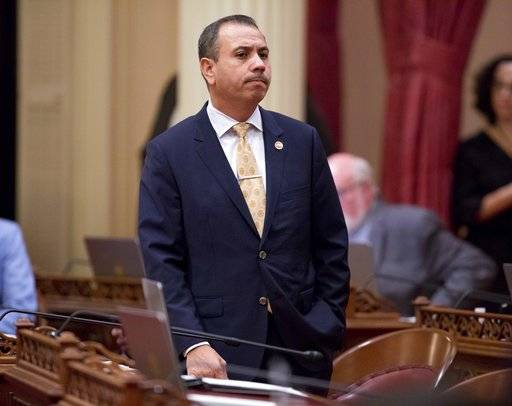 File - In this Jan. 3, 2018 file photo, Sen. Tony Mendoza, D-Artesia, stands at his desk after announcing that he will take a month-long leave of absence while an investigation into sexual misconduct allegations against him are completed during the opening day of the Senate in Sacramento, Calif. Documents released Friday, Feb. 2, 2018, by the California Legislature show four current lawmakers faced sexual misconduct complaints since 2006. The documents outline complaints against Democratic Assemblywoman Autumn Burke of Los Angeles, Republican Assemblyman Travis Allen of Huntington Beach, Democratic Sen. Tony Mendoza of Artesia and Democratic Sen. Bob Hertzberg of Van Nuys.
