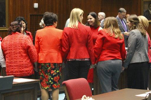 Female members of the Arizona House, from Republican and Democratic parties, hold hands to express support for Rep. Michelle Ugenti-Rita, middle facing camera, as the House prepares to vote to possibly expel a member for sexual harassment in Phoenix, Ariz., Thursday, Feb. 1, 2018. An investigation of Republican Rep. Don Shooter was prompted in an October complaint by Ugenti-Rita, also a Republican.