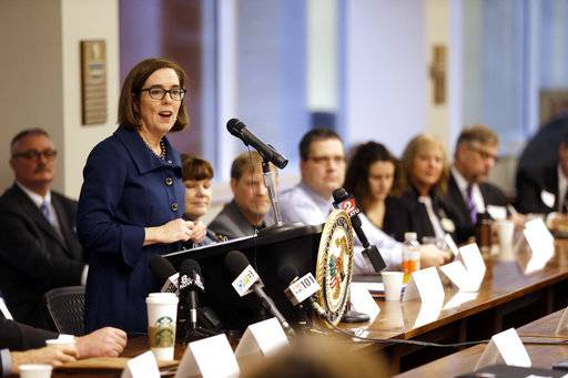 Oregon Gov. Kate Brown , at podium, speaks at a marijuana summit in Portland, Ore., Friday, Feb. 2, 2018. Oregon's top federal prosecutor, Billy J. Williams, is holding the marijuana summit to hear how state, law enforcement, tribal and industry leaders plan to address a pot surplus that he says has wound up on the black market in other states and is fueling crime.