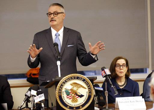 U.S. Attorney for the District of Oregon Billy J. Williams, left, speaks at a marijuana summit in Portland, Ore., Friday, Feb. 2, 2018, as Oregon Gov. Kate Brown sits at right. Oregon's top federal prosecutor, Williams, is holding the marijuana summit to hear how the state, law enforcement, tribal and industry leaders plan to address a pot surplus that he says has wound up on the black market in other states and is fueling crime.