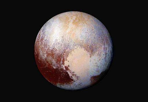 FILE - This image made available by NASA on Friday, July 24, 2015 shows a combination of images captured by the New Horizons spacecraft with enhanced colors to show differences in the composition and texture of Pluto's surface. On Friday, Feb. 2, 2018, The Associated Press has found that stories circulating on the internet claiming Pluto has been officially reclassified as a planet are untrue.  (NASA/JHUAPL/SwRI via AP)