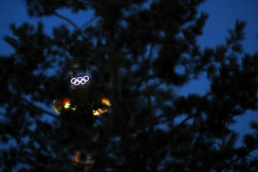 Illuminated Olympic rings atop the Alpensia Ski Jumping Center shine through tree branches at the Alpensia resort prior to the 2018 Winter Olympics in Pyeongchang, South Korea, Friday, Feb. 2, 2018.