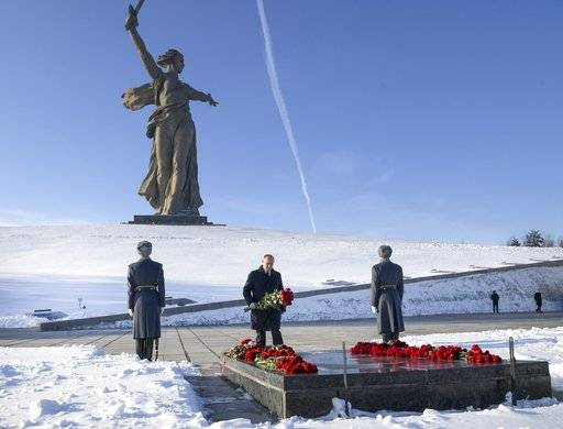 Russian President Vladimir Putin, center, lays flowers at the monument to Motherland during ceremonies marking the 75th anniversary of the Battle of Stalingrad in the southern Russian city of Volgograd, once known as Stalingrad, Russia, Friday, Feb. 2, 2018. The five months of fighting in Stalingrad between August 1942 and February 1943 is regarded as the bloodiest war battle in history. The death toll for soldiers and civilians was about 2 million. Most of the city was reduced to rubble before Nazi forces surrendered on Feb. 2, 1943. (Alexei Druzhinin, Sputnik, Kremlin Pool Photo via AP)
