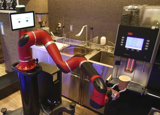 "Robot barista named ""Sawyer"" makes a coffee at Henn-na Cafe, meaning ""Strange Cafe"" in Japanese, in Tokyo, Friday, Feb. 2, 2018. The cafe's robot barista brews and serves coffee as the rapidly aging country seeks to adapt to shrinking workforce. The arm robot ""Sawyer"" debuted this week in Tokyo's downtown business and shopping district of Shibuya."