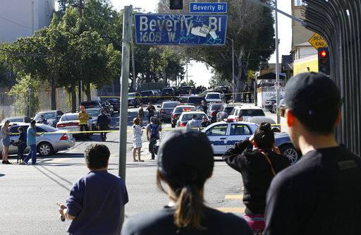 People wait for news outside the Belmont High School complex in Los Angeles Thursday, Feb. 1, 2018. Two students were shot and wounded, one critically, inside a Los Angeles middle school classroom Thursday morning and police arrested a female student believed to be 12 years old, authorities said. The school has about 365 students in grades 6 through 8 and most are Hispanic and many from low-income families.