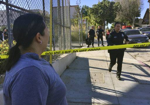 Gloria Echeverria watches as Los Angeles police officers close off a street where a shooting occurred at a middle school in Los Angeles on Thursday, Feb. 1, 2018. Two students were shot inside the middle school classroom Thursday morning and police arrested a female student suspect, authorities said.