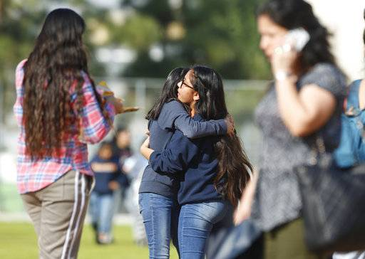 Students hug as people pick up students after a shooting at the Salvador B. Castro Middle School near downtown Los Angeles Thursday, Feb. 1, 2018. A girl opened fire Thursday in a middle school classroom on Thursday, authorities said.