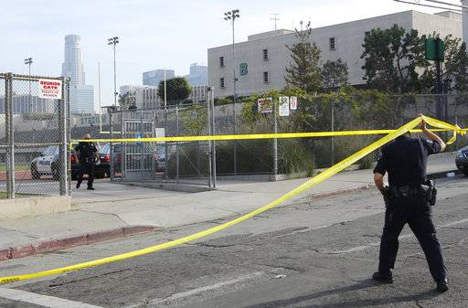 A Los Angeles police school officer walks under yellow tape at the Salvador B. Castro Middle School near downtown Los Angeles Thursday, Feb. 1, 2018. Students at the Los Angeles middle school have been reunited with their parents after a shooting that left a teen critically wounded and several other children injured.