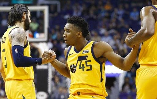 After being fouled on a 3-point basket, Utah Jazz guard Donovan Mitchell (45) is helped up off the floor by guards Ricky Rubio (3) and Joe Johnson, right, during the first half of an NBA basketball game Friday, Feb. 2, 2018, in Phoenix.
