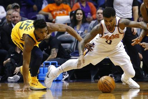 Phoenix Suns forward Marquese Chriss (0) and Utah Jazz guard Donovan Mitchell (45) dive after a loose ball during the first half of an NBA basketball game Friday, Feb. 2, 2018, in Phoenix.