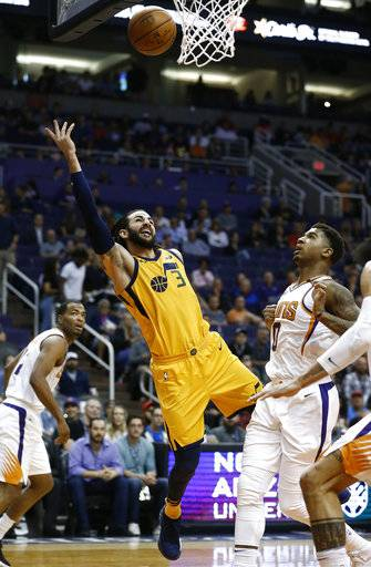 Utah Jazz guard Ricky Rubio (3) gets off a shot as Phoenix Suns forwards Marquese Chriss (0) and TJ Warren, left, watch during the first half of an NBA basketball game Friday, Feb. 2, 2018, in Phoenix.