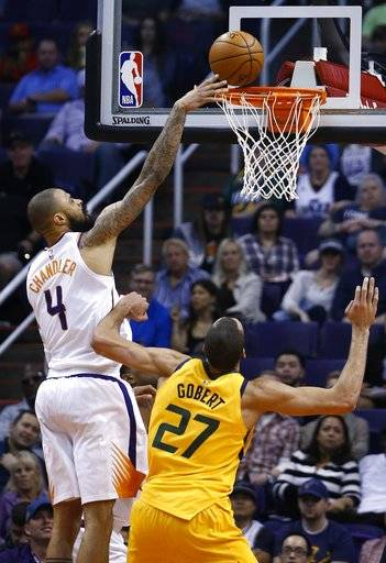Phoenix Suns center Tyson Chandler (4) tips the ball in for a score over Utah Jazz center Rudy Gobert (27) during the first half of an NBA basketball game Friday, Feb. 2, 2018, in Phoenix.