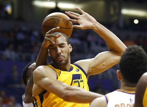 Utah Jazz center Rudy Gobert, middle, gets fouled by Phoenix Suns guard Troy Daniels, rear, during the first half of an NBA basketball gam  Friday, Feb. 2, 2018, in Phoenix.