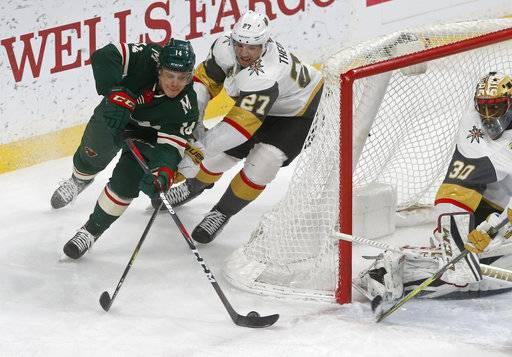 Minnesota Wild's Joel Eriksson Ek, left, of Sweden, tries for a wraparound as Vegas Golden Knights' Shea Theodore and goalie Malcolm Subban, right, defend during the first period of an NHL hockey game Friday, Feb. 2, 2018, in St. Paul, Minn.