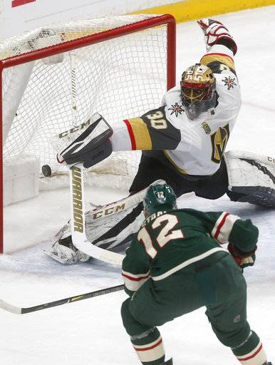 Minnesota Wild's Eric Staal, front, scores on Vegas Golden Knights goalie Malcolm Subban during the first period of an NHL hockey game Friday, Feb. 2, 2018, in St. Paul, Minn.