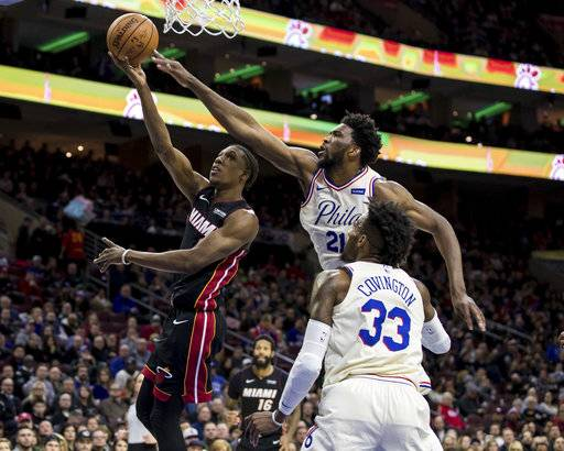 Miami Heat's Josh Richardson, left, shoots as Philadelphia 76ers' Joel Embiid, center, defends while Robert Covington, right, watches during the first half of an NBA basketball gam  Friday, Feb. 2, 2018, in Philadelphia.