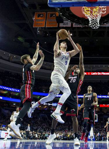 Philadelphia 76ers' Dario Saric, center, goes to the basket between Miami Heat's Tyler Johnson, left, and Justise Winslow during the first half of an NBA basketball game Friday, Feb. 2, 2018, in Philadelphia.