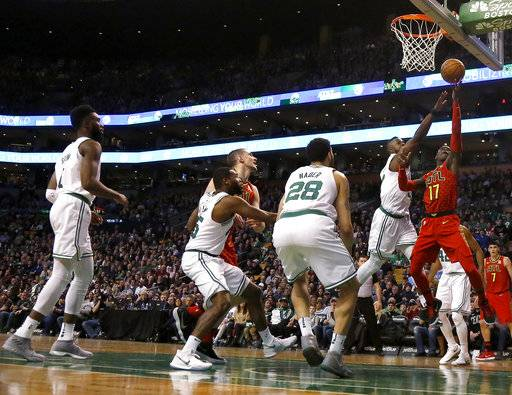 Atlanta Hawks guard Dennis Schroeder (17) drives to the basket ahead of Boston Celtics guard Terry Rozier (12) as Celtics forward Abdel Nader (28) waits for a rebound during the first half of an NBA basketball game Friday, Feb. 2, 2018, in Boston.