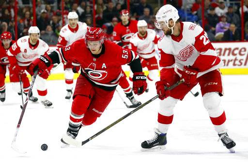 Carolina Hurricanes' Jeff Skinner (53) has the puck poked away by Detroit Red Wings' Mike Green (25) during the second period of an NHL hockey game Friday, Feb. 2, 2018, in Raleigh, N.C.