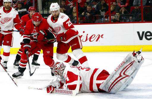 Detroit Red Wings goaltender Petr Mrazek (34) dives for the puck in front of a charging Carolina Hurricanes' Marcus Kruger (16) and Detroit Red Wings' Mike Green (25) during the second period of an NHL hockey game Friday, Feb. 2, 2018, in Raleigh, N.C.