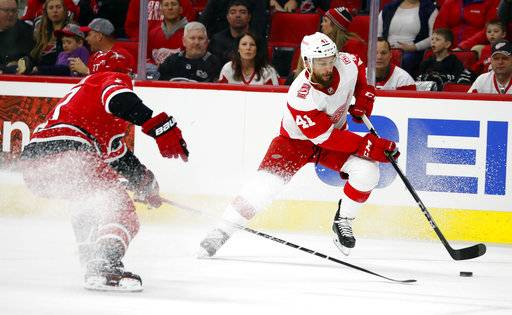 Detroit Red Wings' Luke Glendening (41) moves the puck against Carolina Hurricanes' Justin Faulk (27) during the first period of an NHL hockey game Friday, Feb. 2, 2018, in Raleigh, N.C.