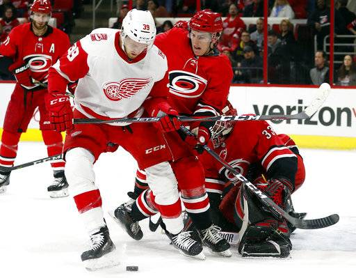 Detroit Red Wings' Anthony Mantha (39) and Carolina Hurricanes' Haydn Fleury (4) work for the puck near the Carolina goal during the first period of an NHL hockey game Friday, Feb. 2, 2018, in Raleigh, N.C.