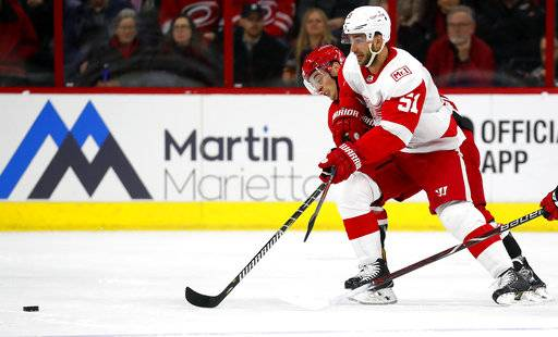 Carolina Hurricanes' Derek Ryan, rear, works against Detroit Red Wings' Frans Nielsen (51) for the puck during the first period of an NHL hockey game Friday, Feb. 2, 2018, in Raleigh, N.C.