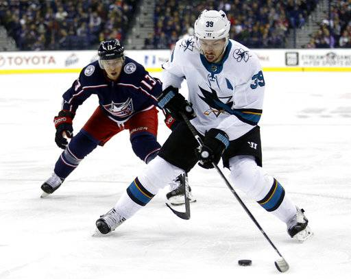 San Jose Sharks forward Logan Couture, right, controls the puck against Columbus Blue Jackets forward Cam Atkinson during the first period of an NHL hockey game in Columbus, Ohio, Friday, Feb. 2, 2018.