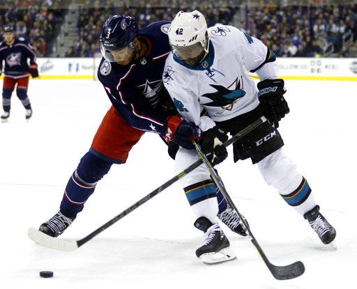 Columbus Blue Jackets defenseman Seth Jones, left, works for the puck against San Jose Sharks forward Joel Ward during the first period of an NHL hockey game in Columbus, Ohio, Friday, Feb. 2, 2018.