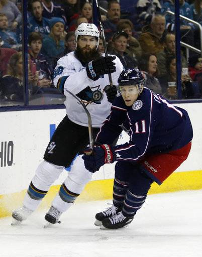 San Jose Sharks defenseman Brent Burns, left, clears the puck next to Columbus Blue Jackets forward Matt Calvert during the second period of an NHL hockey game in Columbus, Ohio, Friday, Feb. 2, 2018.