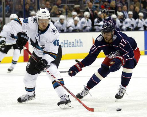 San Jose Sharks forward Tomas Hertl, left, of the Czech Republic, passes the puck against Columbus Blue Jackets forward Brandon Dubinsky during the second period of an NHL hockey game in Columbus, Ohio, Friday, Feb. 2, 2018.