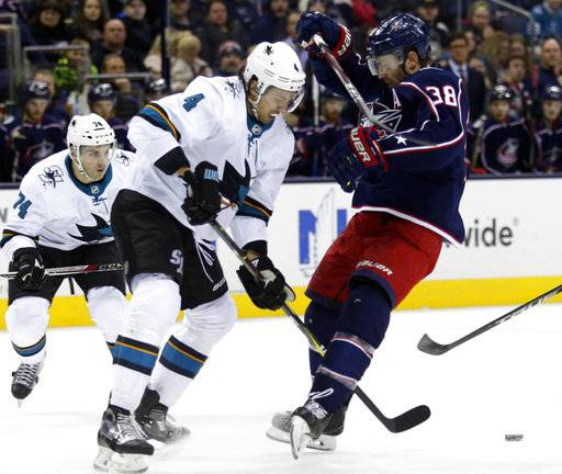 San Jose Sharks defenseman Brenden Dillon reaches for the puck on the other side of Columbus Blue Jackets forward Boone Jenner during the second period of an NHL hockey game in Columbus, Ohio, Friday, Feb. 2, 2018.