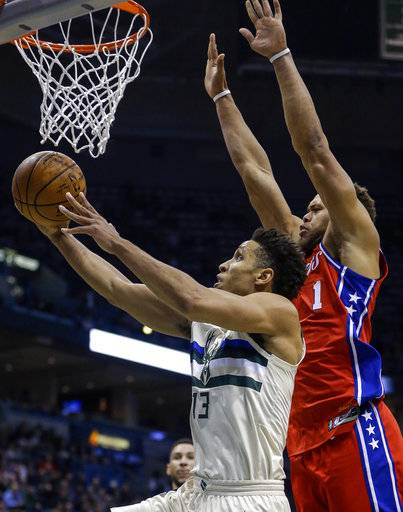 Milwaukee Bucks' Malcolm Brogdon, left, puts up a reverse layup as Philadelphia 76ers' Justin Anderson tries to defend during the second half of an NBA basketball game Monday, Jan. 29, 2018, in Milwaukee.