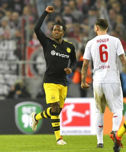 Dortmund's new forward Michy Batshuayi celebrates beside Cologne's Marco Hoeger after scoring the opening goal during the German Bundesliga soccer match between 1. FC Cologne and Borussia Dortmund in Cologne, Germany, Friday, Feb. 2, 2018.