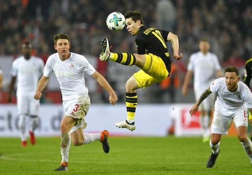 Dortmund's Raphael Guerreiro jumps for the ball during the German Bundesliga soccer match between 1. FC Cologne and Borussia Dortmund in Cologne, Germany, Friday, Feb. 2, 2018.