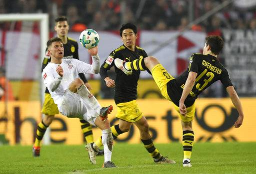 Cologne's Salih Ozcan, left, and Dortmund's Raphael Guerreiro, right, challenge for the ball during the German Bundesliga soccer match between 1. FC Cologne and Borussia Dortmund in Cologne, Germany, Friday, Feb. 2, 2018.