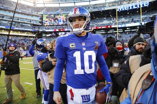 FILE - In this Dec. 31, 2017, file photo, New York Giants quarterback Eli Manning (10) walks off the field after an NFL football game against the Washington Redskins in East Rutherford, N.J. After coming off the worst season of his professional career, Manning is looking ahead.