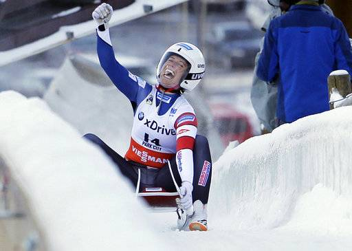 FILE - In this Dec. 17, 2016, file photo, second-place finisher Emily Sweeney, of the United States, celebrates as she slides to the finish after a women's World Cup Luge sprint event in Park City, Utah. For whatever reason, sliding sports have always gotten tons of attention from the military, and the team that is wearing red, white and blue in Korea has plenty of people who wear the flag at work as well. Sweeney is in the Army.