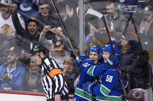 Vancouver Canucks' Bo Horvat and Brendan Gaunce, right, celebrate Gaunce's goal against the Chicago Blackhawks as referee Dave Jackson skates past during the second period of an NHL hockey game Thursday, Feb. 1, 2018, in Vancouver, British Columbia. (Darryl Dyck/The Canadian Press via AP)