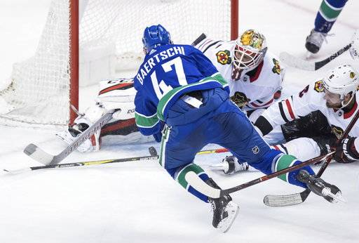 Vancouver Canucks' Sven Baertschi (47), of Switzerland, is stopped by Chicago Blackhawks goalie Anton Forsberg, of Sweden, as Michal Kempny, right, of the Czech Republic, defends during the third period of an NHL hockey game Thursday, Feb. 1, 2018, in Vancouver, British Columbia. (Darryl Dyck/The Canadian Press via AP)