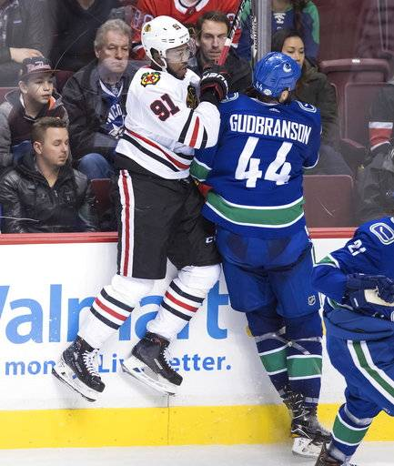 Chicago Blackhawks' Anthony Duclair, left, and Vancouver Canucks' Erik Gudbranson collide during the third period of an NHL hockey game Thursday, Feb. 1, 2018, in Vancouver, British Columbia. (Darryl Dyck/The Canadian Press via AP)