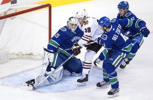 Chicago Blackhawks' Jonathan Toews (19) is stopped by Vancouver Canucks goalie Jacob Markstrom, left, of Sweden, as Michael Del Zotto (4) and Troy Stecher (51) defend during the second period of an NHL hockey game Thursday, Feb. 1, 2018, in Vancouver, British Columbia. (Darryl Dyck/The Canadian Press via AP)